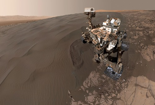 "This self-portrait of NASA's Curiosity Mars rover shows the vehicle at ""Namib Dune,"" where the rover's activities included scuffing into the dune with a wheel and scooping samples of sand for laboratory analysis. The scene combines 57 images taken on Jan. 19, 2016, during the 1,228th Martian day, or sol, of Curiosity's work on Mars. The camera used for this is the Mars Hand Lens Imager (MAHLI) at the end of the rover's robotic arm. Namib Dune is part of the dark-sand ""Bagnold Dune Field"" along the northwestern flank of Mount Sharp. Images taken from orbit have shown that dunes in the Bagnold field move as much as about 3 feet (1 meter) per Earth year. (NASA / JPL-Caltech / MSSS)"