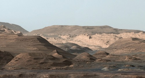 This composite image looking toward the higher regions of Mount Sharp was taken on September 9, 2015, by NASA's Curiosity rover. In the foreground -- about 2 miles (3 kilometers) from the rover -- is a long ridge teeming with hematite, an iron oxide. Just beyond is an undulating plain rich in clay minerals. And just beyond that are a multitude of rounded buttes, all high in sulfate minerals. The changing mineralogy in these layers of Mount Sharp suggests a changing environment in early Mars, though all involve exposure to water billions of years ago. (NASA / JPL-Caltech / MSSS)
