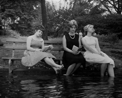 Three women keep cool during a heat wave by moving a park bench into the water in Central Park New York.jpg