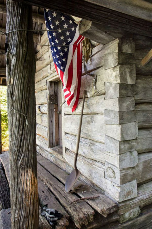 flag hanging off log cabin .jpg